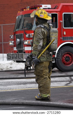 A winter scene of a fireman watching a fire with a fire truck in the background.