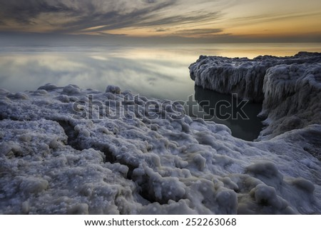 A winter sunrise and shelf ice along the shore of Lake Michigan at Openlands Lakeshore Preserve, Fort Sheridan, Illinois. - stock photo