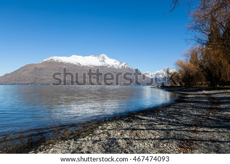 A winter view of Cecil Peak and The Ledge with snow topped peaks from the side of Lake Wakatipu in Queenstown, New Zealand.