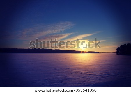 A wintry sunset. An image of a sunset on a cold winter day. Sun is going down behind a lake covered with ice and snow. Some forest is in the background. Image has a strong vintage effect applied.