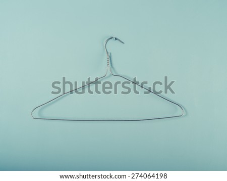 A wire hanger is hanging from a blue wall - stock photo