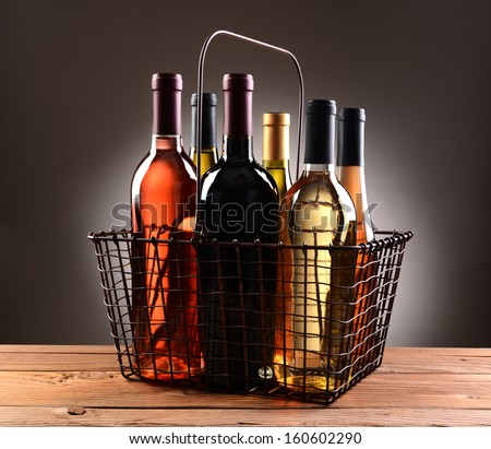 A wire shopping basket filled with assorted wine bottles. The basket is sitting on a rustic wooden table with a light to dark gray spot background.  - stock photo