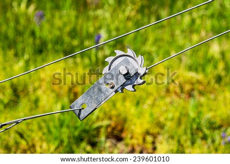 A wire tension device used to increase the tautness of wire fences against a green background. - stock photo