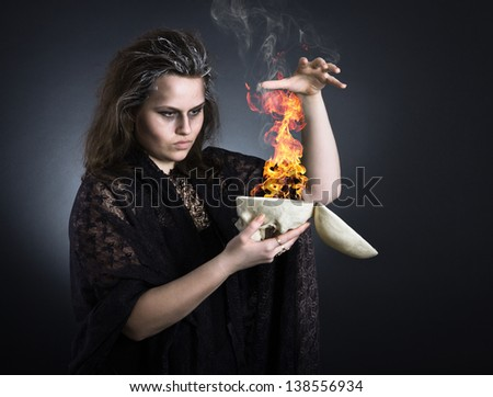 A witch casts a spell with a skull. - stock photo