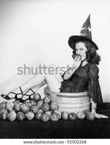 A wizardly woman takes a bite out of a big apple - stock photo