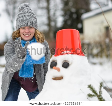 a woman and a snowman with a snowball - stock photo