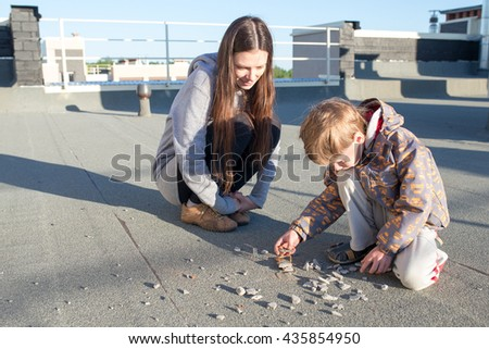 A woman and her son sitting on the roof and play in the rocks. - stock photo