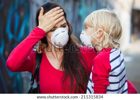 A woman and her son wearing protective face masks for pollution or virus. The woman is suffering from headache or migraine. - stock photo