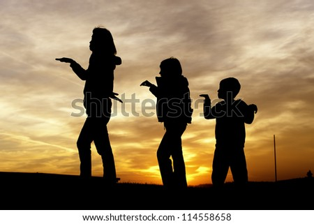 A woman and her two children play around during sunset. - stock photo