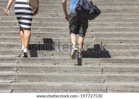 A woman and man climbing on concrete stairs - stock photo
