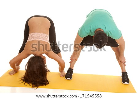 A woman and man doing stretches bending over. - stock photo
