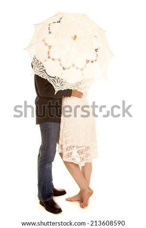 a woman and man hiding behind an umbrella, holding onto each other. - stock photo