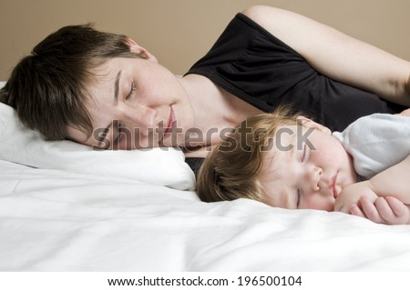 A woman and toddler sleeping beside each other.