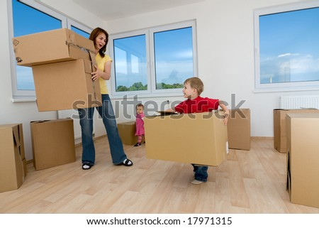 A woman and two children with cardboard boxes in new home.