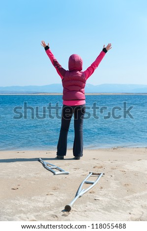 a woman - arms up- stands at a lake, having left her crutches,  back view - stock photo