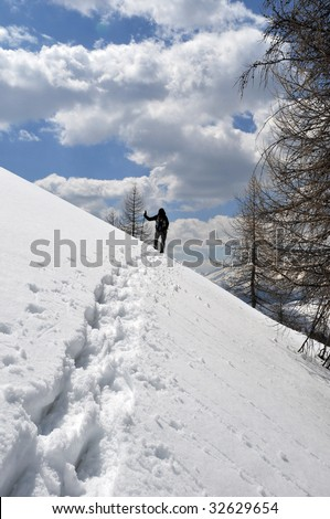 A woman ascend the mountain foot to the snowshoe