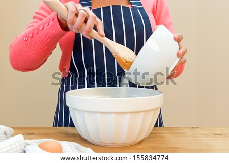 A woman at home in her kitchen making a cake - stock photo