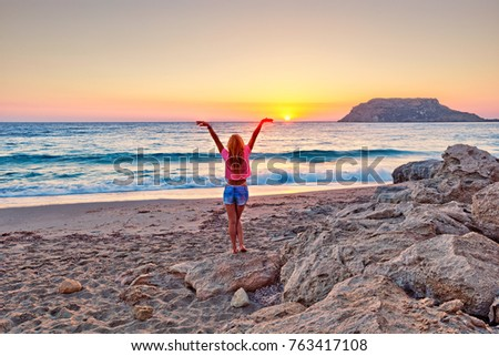 A woman at sunset in Fragolimnionas beach of Karpathos, Greece