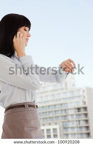 A woman at work checks the time on her watch as she makes a phone call - stock photo