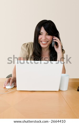 A woman at work using the telephone.