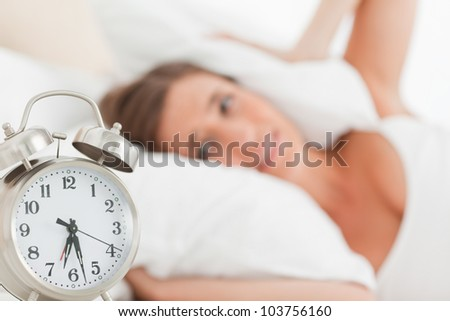 A woman blocks her ears with a pillow as her alarm clock goes off. - stock photo