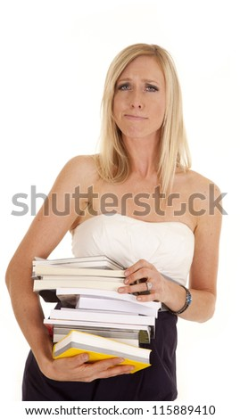 A woman blowing hair off of her face holding on to a stack of books. - stock photo