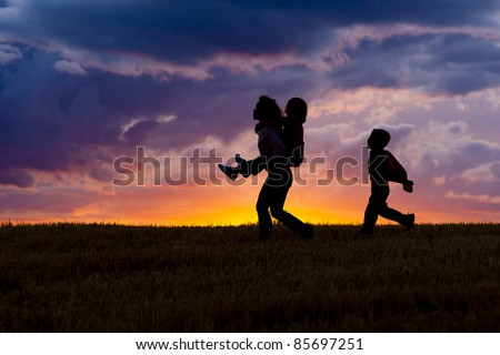 A woman carries her daughter on her back as her son walks behind at sunset. - stock photo