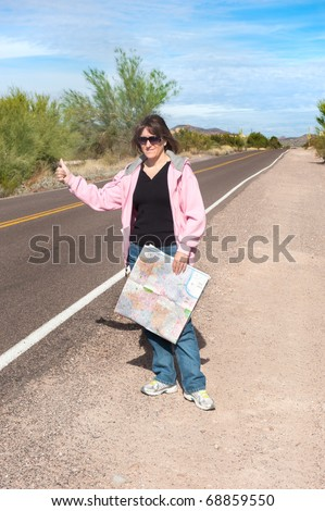 A woman carrying a map hitchhikes on a remote desert roadside.