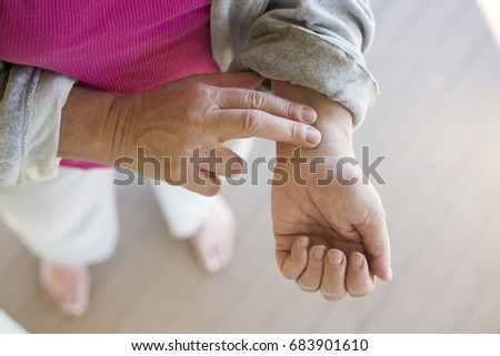 A woman checks her pulse on her wrist.