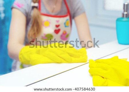 A woman cleaning bath at home. Female washing bathtub in yellow gloves - stock photo