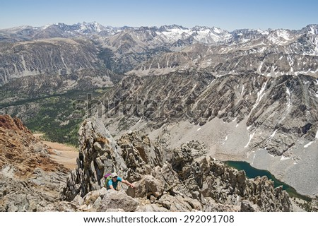 a woman climbing up Mount Emerson in the Sierra Nevada Mountains - stock photo