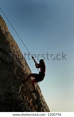 A woman climbs a cliff in California - stock photo