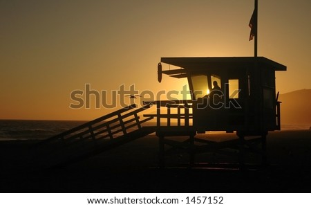 A woman closes the guard tower at sunset on the beach - stock photo