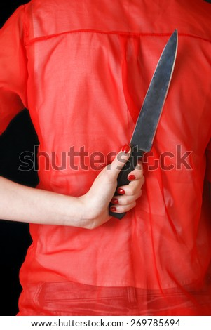A woman conceals a kitchen knife for an unforeseen attack on possible home invaders. - stock photo