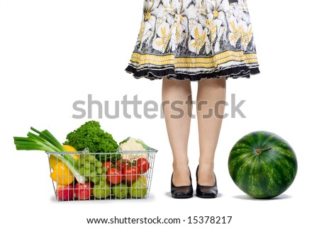 A woman conquers grocery shopping watermelon and a basket full of fresh fruits and veggies. - stock photo