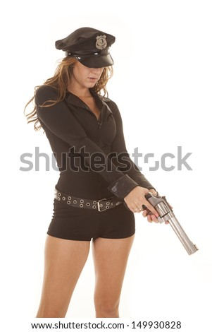 A woman cop holding a gun looking down. - stock photo