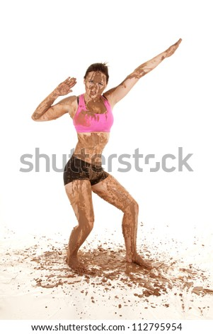 A woman covered in mud striking a pose. - stock photo
