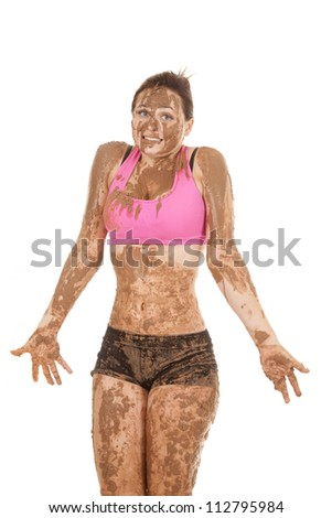 A woman covered in mud with a funny expression on her lips. - stock photo