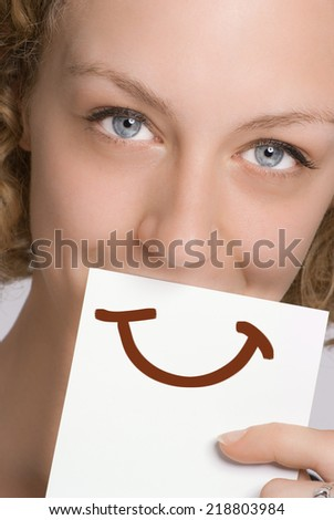 A woman covering her mouth with a piece of paper with a smile painted on it