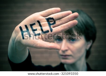 "A woman covers her face with his hand on his hand written in black marker ""help."""