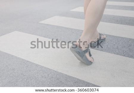 A woman crossing a crosswalk - stock photo