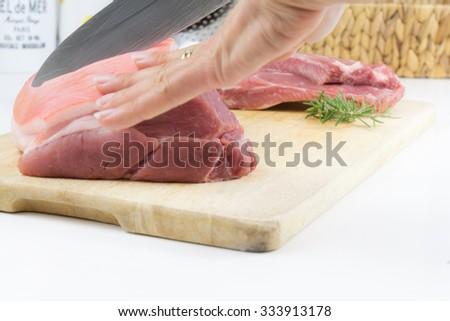 A woman cuts raw pork - a pork roast with crackling - stock photo