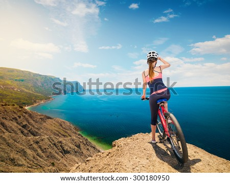 A woman cyclist on a mountain bike looking at the landscape of mountains and sea. Adventure travel on bike.