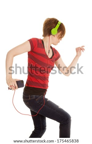 A woman dancing around with her headphones on. Listening to music. - stock photo