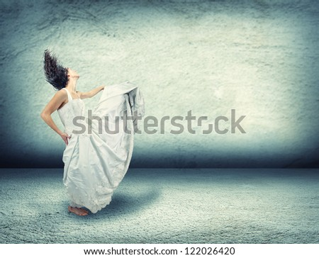 a woman dancing in an empty room made of concrete - stock photo