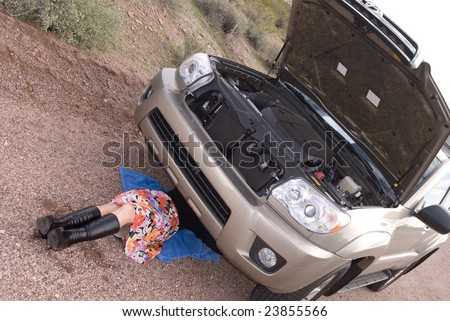 A woman deals with her broken car on a remote dirt road. - stock photo