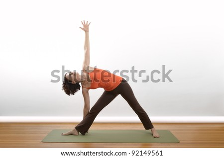A woman demonstrates the Triangle position in yoga. - stock photo