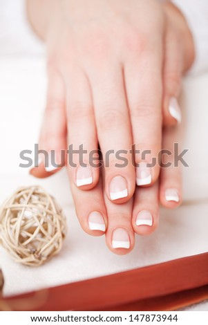 A woman displays her beautifully manicured French nails for the viewer - stock photo