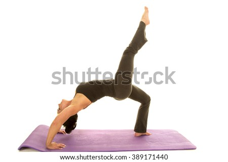 a woman doing a back bend yoga stretch with her leg up. - stock photo