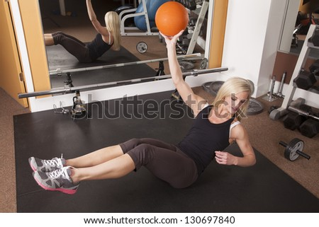 A woman doing a crunch while holding on to a weighted ball.